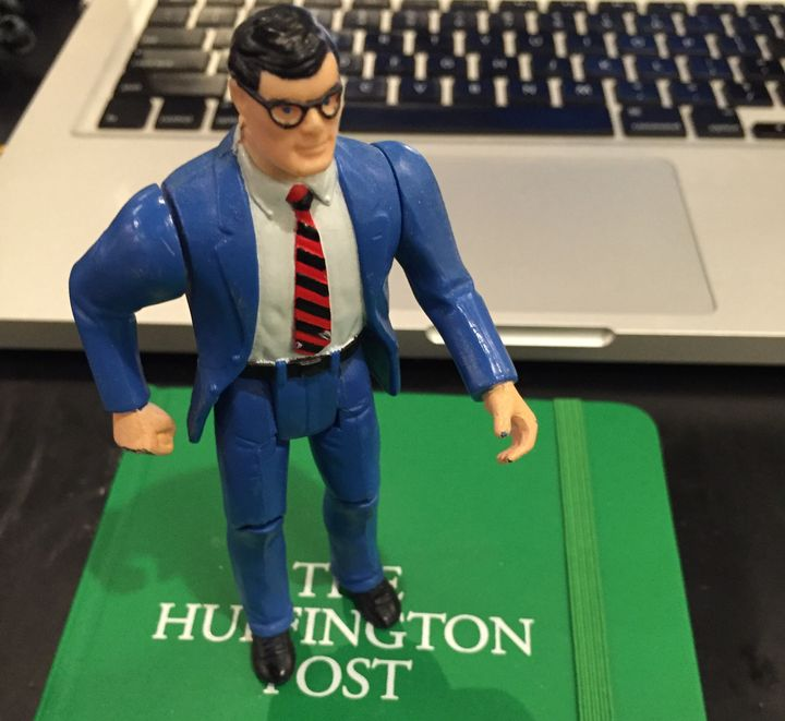 Clark Kent stands proudly atop a HuffPost notebook.