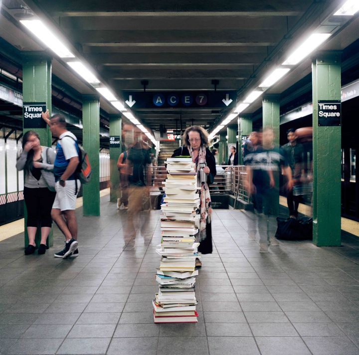 Stack of books left on a Times Square subway platform.