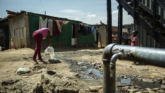 A resident of the Zandspruit informal settlement in Johannesburg empties a bucket of watsed water into a polluted stream next to a communal water tap on March 11, 2015 in Johannesburg, South Africa. Without reforms, the world will be plunged into a water crisis that could be crippling for hot, dry countries, the United Nations warned on March 20, 2015. In an annual report, the UN said abuse of water was now so great that on current trends, the world will face a 40-percent 'global water deficit' by 2030 -- the gap between demand for water and replenishment of it. AFP PHOTO / MUJAHID SAFODIEN        (Photo credit should read MUJAHID SAFODIEN/AFP/Getty Images)