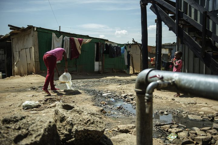 A resident of the Zandspruit informal settlement in Johannesburg empties a bucket of watsed water into a polluted stream next