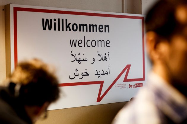 Volunteers in front of awelcome sign at a new jobs counseling center for migrants and refugees...