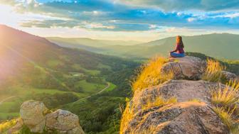 Woman doing yoga on top of a rock in the mountains, meditating in lotus posture, in a beautiful and colorful sunset. Energizing moment with the mother nature.The photo was taken in Santa Catarina State, Brazil.