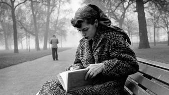 Journalist Katherine Whitehorn reading a book in London's Hyde Park.