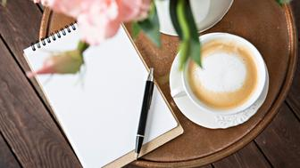 Notebook with a pen on the table next to coffee and flowers