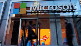 People walk past a Microsoft office in New York on October 6, 2015. Microsoft introduced a pair of big-screen smartphones and a laptop during an event in New York on Tuesday. The company unveiled the Surface Book, a laptop with 13.5-inch detachable touchscreen, the Surface Pro 4 tablet and the Lumia 950 and 950 XL smartphones, which feature displays measuring over 5 inches. The Surface devices launch later this month, while the Lumias arrive in November. AFP PHOTO/JEWEL SAMAD        (Photo credit should read JEWEL SAMAD/AFP/Getty Images)