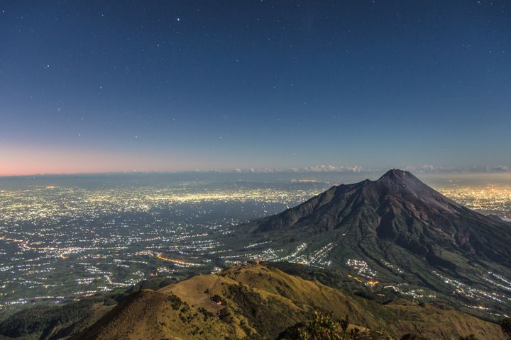 Mount Merapi, a highly active volcano, towers over the city.