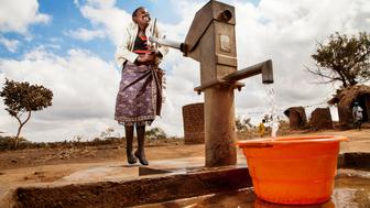 In late July 2015 in Malawi, 12-year-old Kosalata Banda collects water from a recently installed borehole in the village of Chikosa, Dowa District. She lives with her mother, Rhoda January, and two siblings, 2-year-old Tamadani January and 8-year-old John Banda. The family uses 100 litres of water daily: 40 litres for bathing, 20 for cooking and drinking, 20 for washing clothes and 20 for washing dishes. Before the installation of the borehole, their water came from shallow wells. ìThe water was really bad,î said Ms. January. ìSometimes, you could see the germs with your eyes. We were supposed to add chemicals to clean it, but we are so poor we couldnít afford it. People were getting diarrhoea, dysentery and even cholera. We got a borehole in 2011, and since then, people donít get sick because of the water.î She continued, ìI love using water when I cook Nsima [a dish made of maize and water]. That is my favourite. Itís what weíve eaten since we were young, so weíve known it all our lives. So we love it.î Kosalata said, ìI love washing clothes, especially the bedding. Clean bedding is hygienic, and it feels nice and smells nice.î Ms. Januaryís oldest two children attend school while she works as a subsistence famer, growing cowpeas and maize. Her first husband ñ father to her two oldest children ñ died of stomach ulcers in 2009. She remarried in 2011, becoming the second wife of her new husband, Tamadaniís father. He spends the majority of his time away from Ms. Januaryís home, with his first wife.