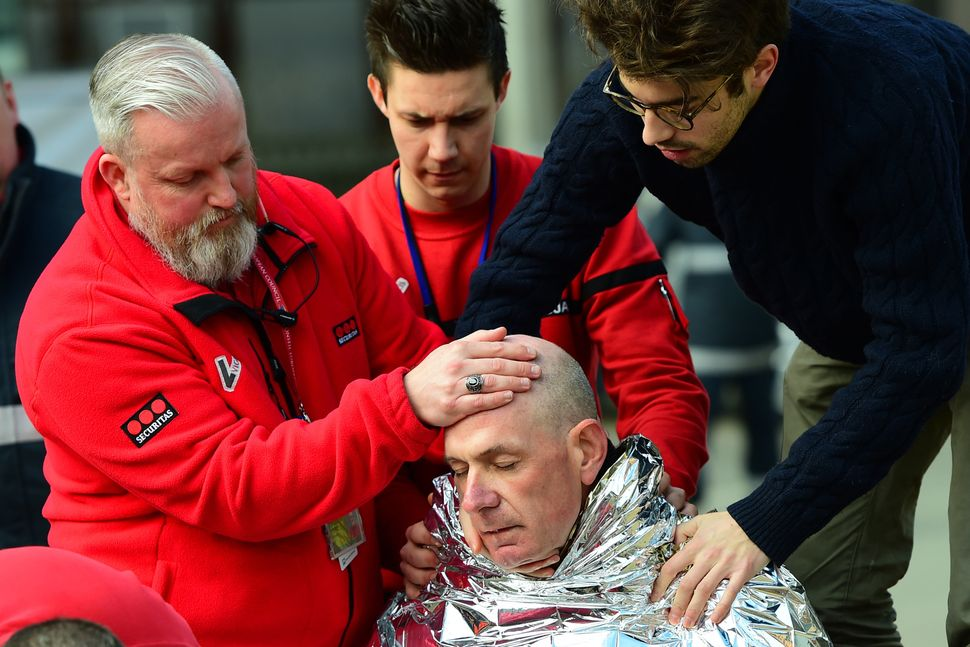 Rescuers give avictim first aid on March 22, 2016, near Maalbeek metro station in Brussels.