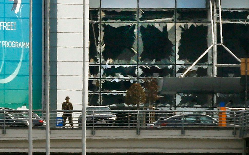 A soldier stands near broken windows after explosions at Zaventem airport near Brussels, Belgium, March 22, 2016.