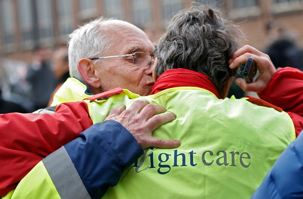 Airport workers embrace as they leave the scene of explosions at Zaventem airport near Brussels, Belgium, March 22, 2016.&nbs