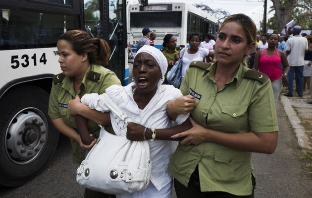 A member of the Ladies in White, a group founded by partners and relatives of jailed dissidents, is led...