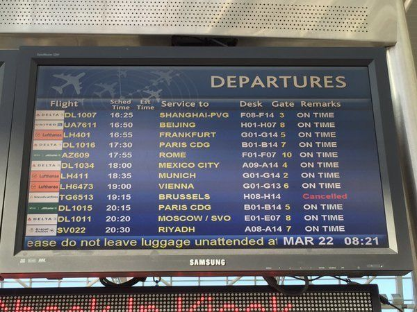A list of departures at New York's JFK Airport shows a Brussels-bound flight canceled.
