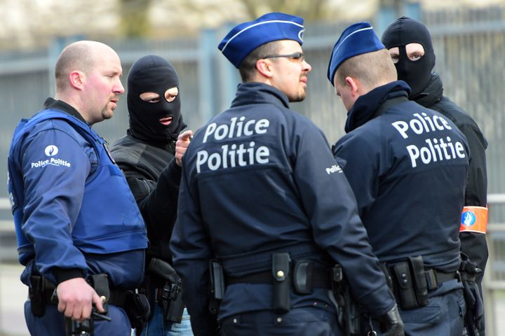 Policemen speak at a security perimeter near Maalbeek metro station on March 22, 2016, in Brussels, after a blast at this sta