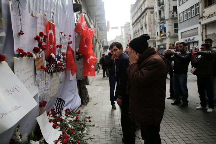 A man reacts in front of a makeshift memorial at the location of the blast of a suicide attack on Istiklal Street, a major sh