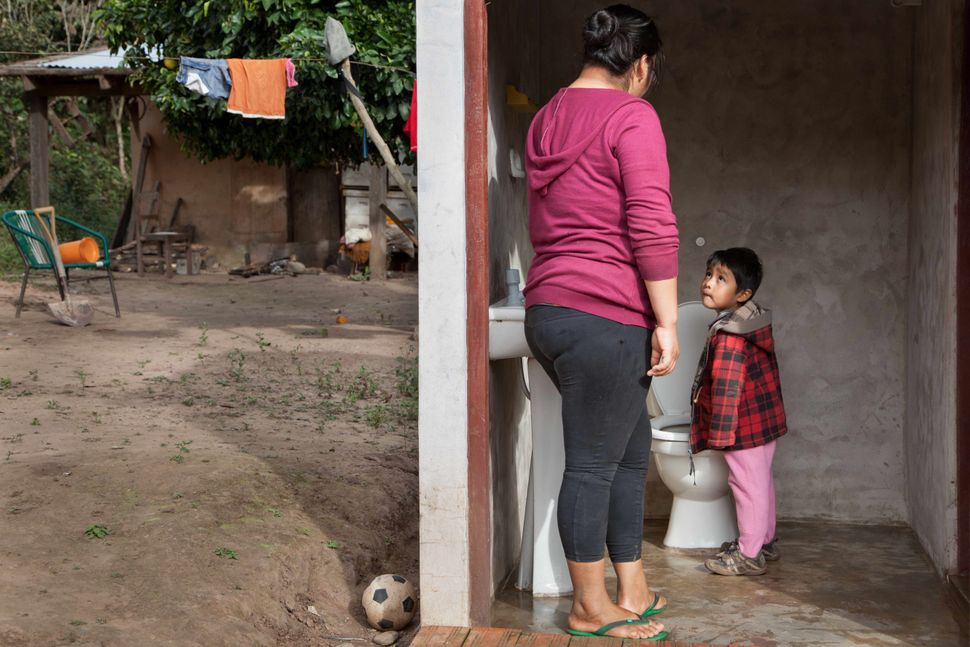 Aidi Panoso toilet trains 3-year-old Mateo Visalla, one of her twin sons, at home in Totorenda, a Guaraní community in
