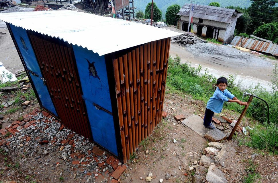 A student washes his hands outside a toilet in a UNICEF-supported temporary learning center in Dolakha, one of the districts