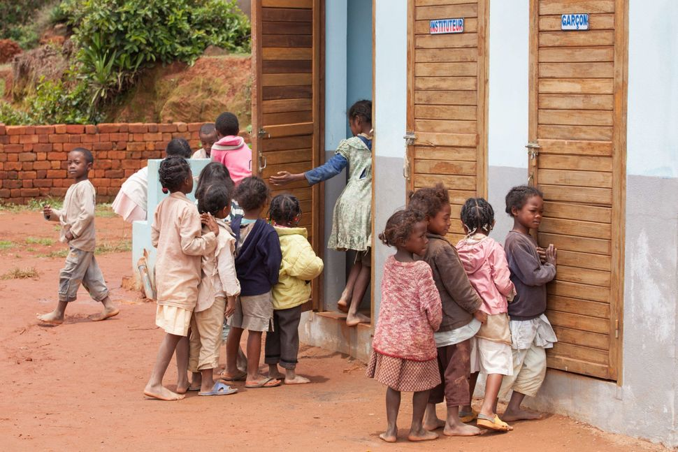 Girls wait in line to use latrines at the Lohanosy Primary School in Madagascar. A lack of separate toilets often leads girls