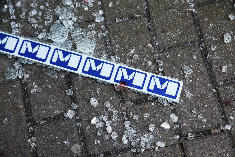Broken glass and blood is seen beside signage outside an entrance to Maelbeek metro station following an attack on March 22,
