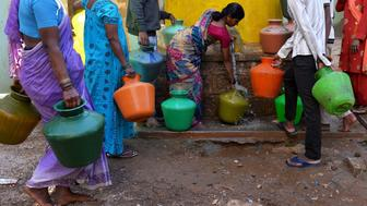 This photo taken on March 18, 2015 shows residents in Bangalore collecting drinking water in plastic pots from a community tap. A new UN report launched in New Delhi on March 20 ahead of World Water Day on March 22 warned of an urgent need to manage the world's water more sustainably and highlight the problem of groundwater over-extraction, particularly in India and China.  The report says global demand for water is increasing exponentially, driven largely by population growth.  AFP PHOTO / Manjunath KIRAN        (Photo credit should read MANJUNATH KIRAN/AFP/Getty Images)