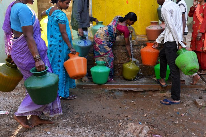 This photo taken on March 18, 2015 shows residents in Bangalore collecting drinking water in plastic pots from a community ta