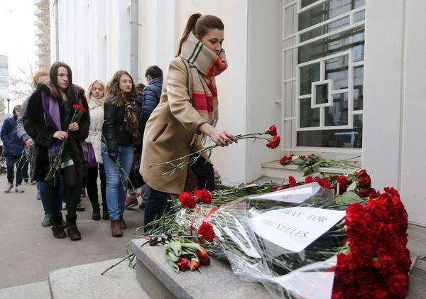 People place flowers for the victims of the Brussels attacks, in front of the Belgian embassy in Moscow, Russia, March 22, 20