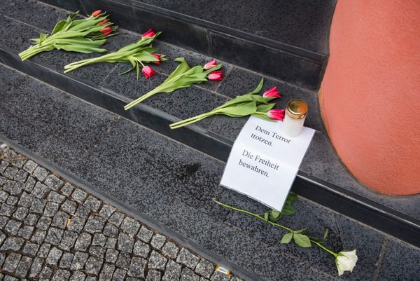 """Thesign by these flowers outside the Belgium embassy in Berlin reads, """"Defy terror, protect freedom."""""""
