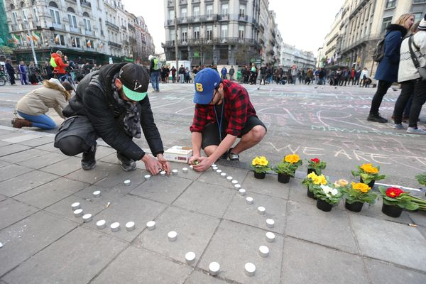 People leave candles and flowers in tribute to victims of triple bomb attacks in front of the stock exchange building in the