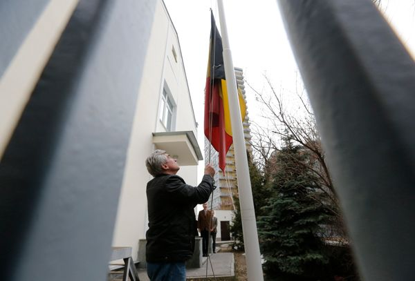 An embassy worker moves the Belgian flag to half mast in tribute to victims of the Brussels attacks, at the Belgian embassy i
