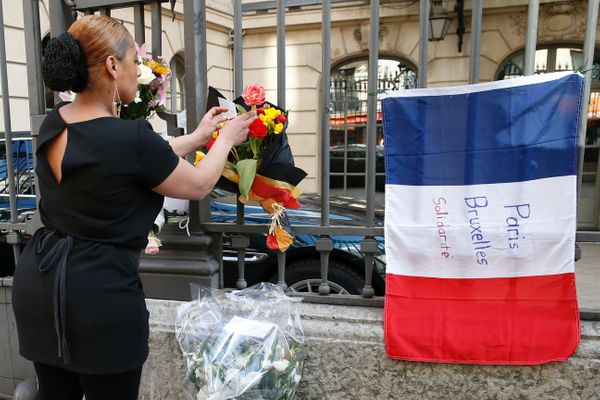 A woman leaves a bouquet of flowers in the Belgian national colors next to a French national flag with the lettering 'Paris -