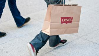 A shopper carries goods in a Levi Strauss & Co. paper bag at the Odysseum shopping center in Montpellier, France, on Wednesday, Dec. 4, 2013. The euro area's nascent economic recovery lost momentum in the third quarter as growth in Germany slowed and France's economy unexpectedly contracted. Photographer: Balint Porneczi/Bloomberg via Getty Images