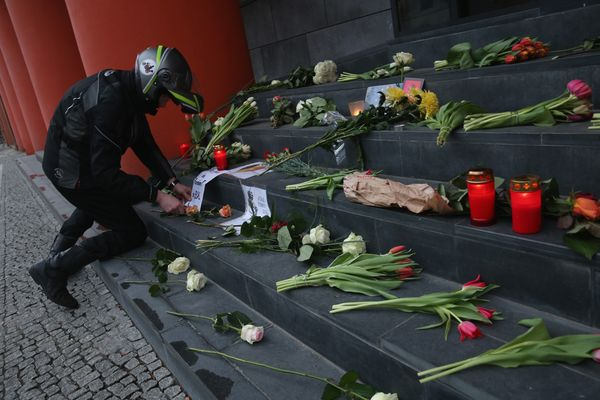 A motorcyclist lays flowers at the steps of the Belgian Embassy following the terrorist attacks in Brussels on March 22, 2016