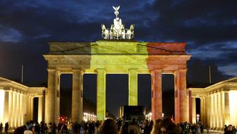 People stand in front of the Brandenburg gate, which is illuminated in black, yellow and red in the colours of the Belgian flag in tribute to victims of Tuesday's attacks in Brussels, in Berlin, Germany, March 22, 2016.        REUTERS/Fabrizio Bensch - RTSBQUO