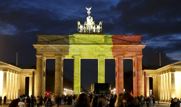 People stand in front of the Brandenburg Gate,in Berlin, Germany, which is illuminated in black, yellow and red in the