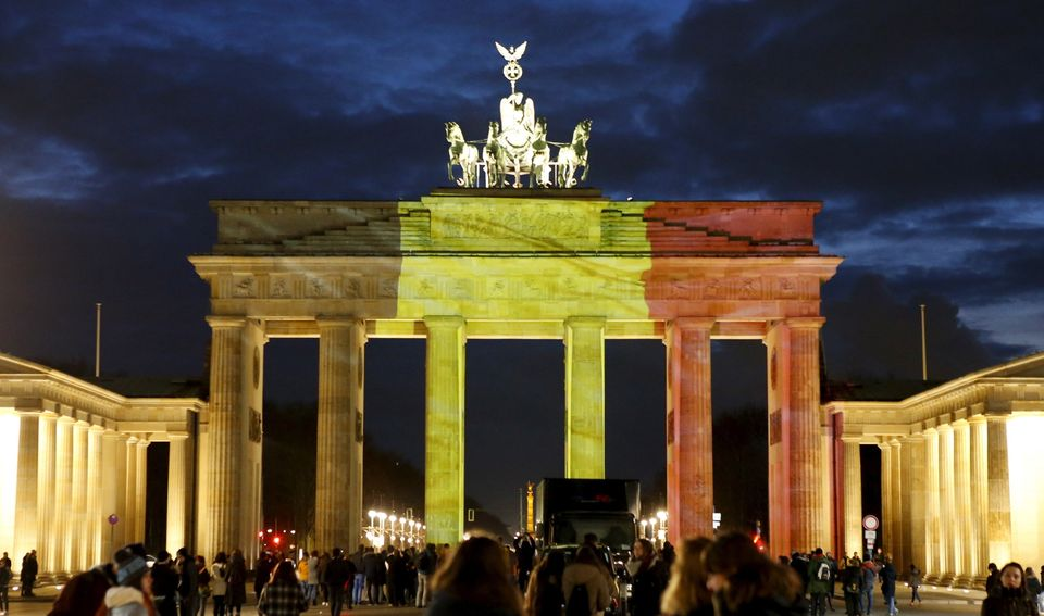 People stand in front of the Brandenburg Gate, in Berlin, Germany, which is illuminated in black, yellow and red in the