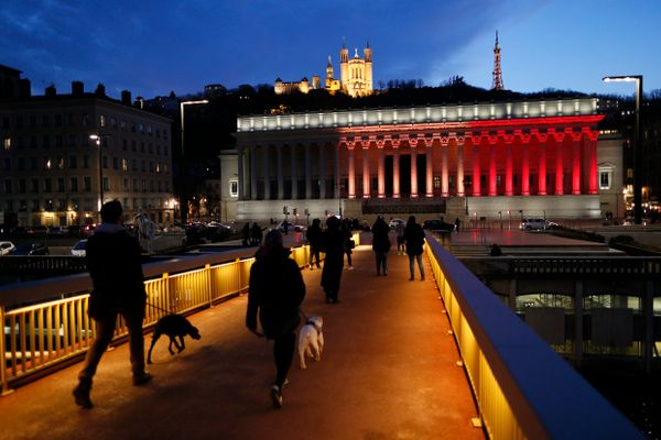 The black, yellow, and red colors of the Belgian flag are projected on the courthouse in Lyon, France, in tribute to the vict