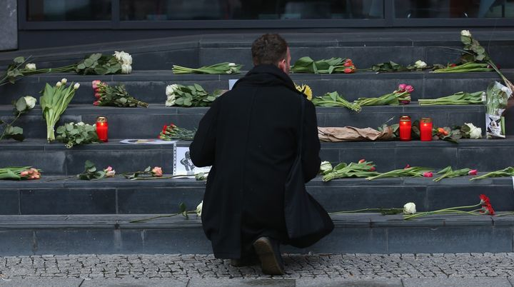 A man lays flowers at the steps of the Belgian Embassy in Berlin. World leaders reacted with shock and solidarity after the a