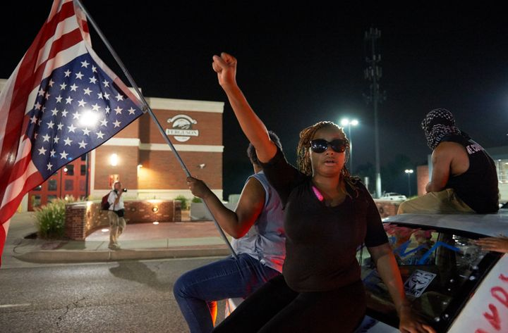 A protester holds their first in the air outside of the Ferguson Police Department in Missouri.