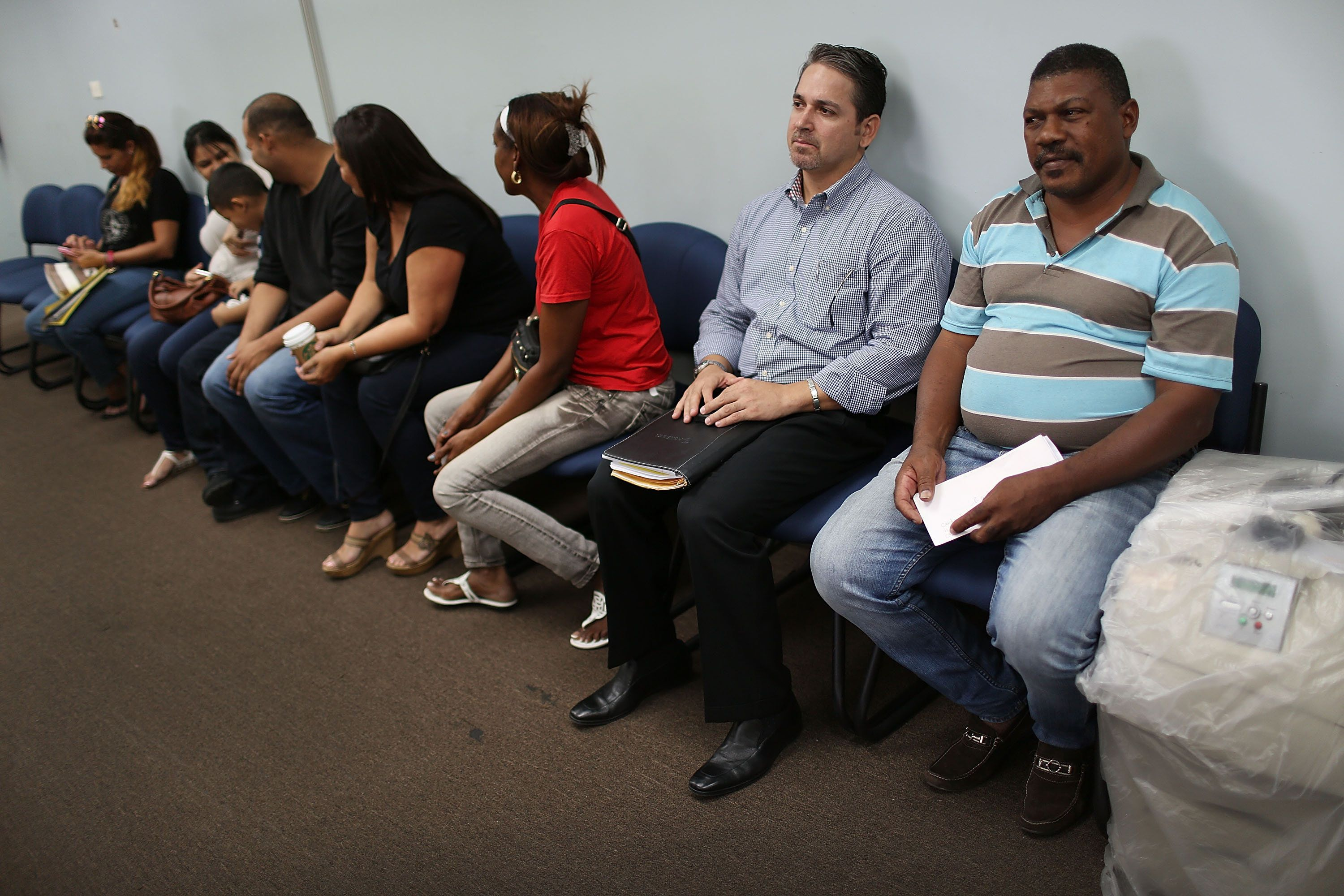 SAN JUAN, PUERTO RICO - JUNE 30:   Rolando Santiago (2nd R), who lost his job at pharmacutical company, along with other people wait for help at an unemployment office a day after Puerto Rican Governor Alejandro Garcia Padilla gave a televised speech regarding the governments $72 billion debt on June 30, 2015 in San Juan, Puerto Rico.  The Governor said in his speech that the people will have to sacrifice and share in the responsibilities for pulling the island out of debt.  (Photo by Joe Raedle/Getty Images)