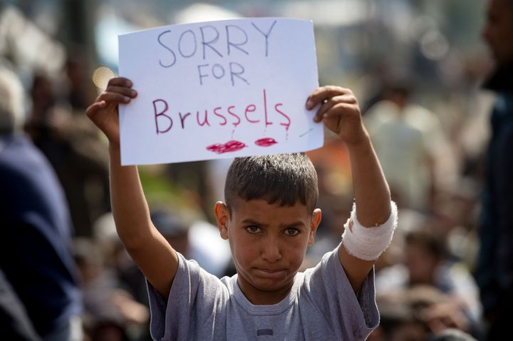 A boy holds a placard expressing sympathy for the victims of the terror attacks in Brussels during a protest at a makeshift c