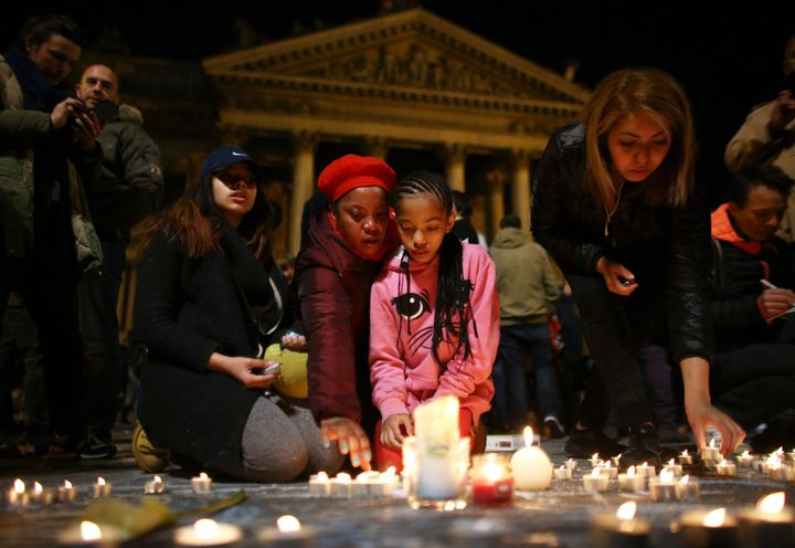 A young girl lights a candle for the attack victims at the Place de la Bourse in Brussels. Some began to sing John Lennon's I