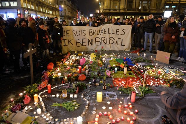 Belgian people light candles as they gather to commemorate victims of terror attack at the Place de la...