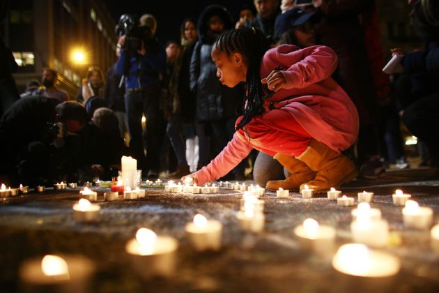 A young girl lights a candle at the Place de la Bourse following today's attacks on March 22, 2016 in...