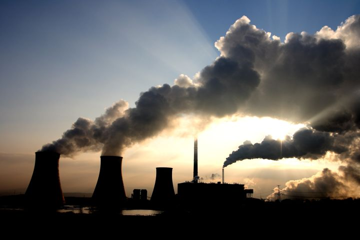 Steam rises from the cooling towers of a coal-fired power plant. Burning coal is one of the human activities t