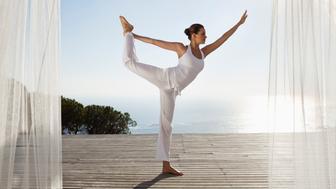 Teenage girl exercising against clear sky