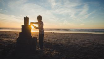 A 9 year old boy is putting some final touches on a very large sandcastle. He is on a beach in San Diego, California. The sun is setting behind him and there is some lens flare surrounding him and the castle.