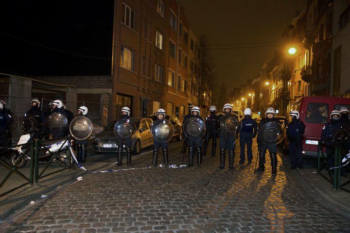 Policemen stand guard the street at Rue de la Carpe in Molenbeek-Saint-Jean in Brussels, on March 19, 2016.