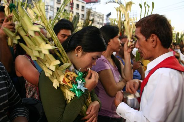 A devotee carrying palm fronds receives the holy Communion in Quiapo, Mexico on March 20.