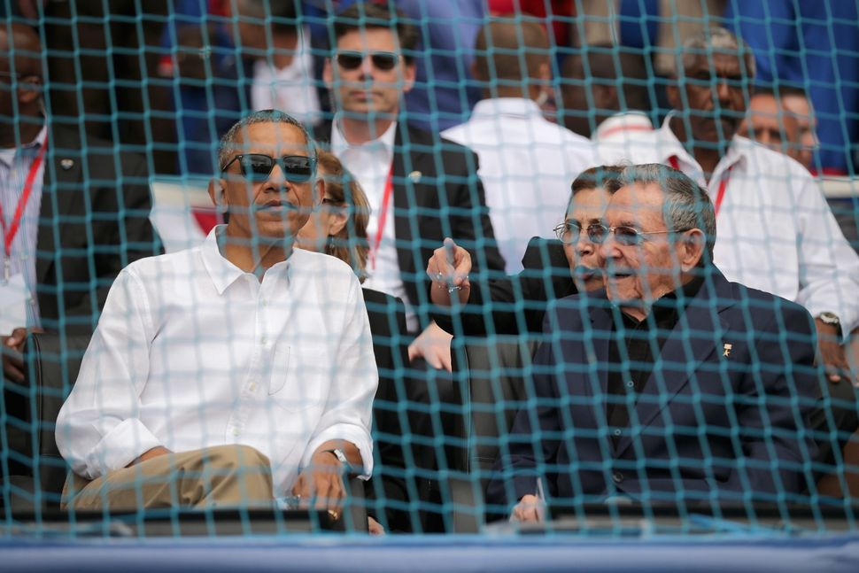 Presidents Barack Obama and Raúl Castro talk before the start of a game between the Tampa Bay Rays and Cuba's national