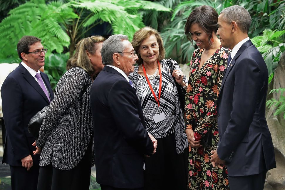 Presidents Raúl Castro and Barack Obama, accompanied by U.S. first lady Michelle Obama, speak with the help