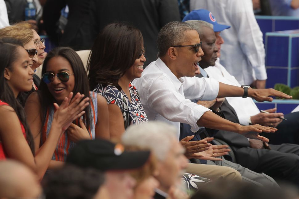 President Barack Obama and his family react to the first run scored during the baseball game between the Tampa Bay Rays and C